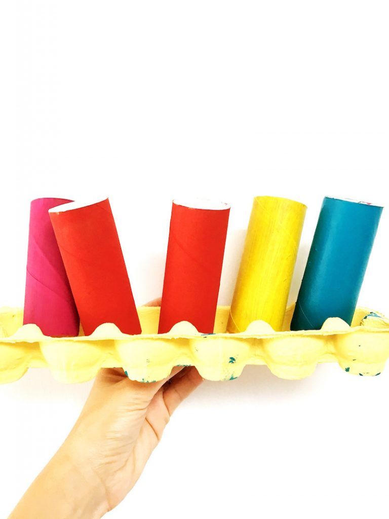 An egg tray containing upright painted toilet tubes for a fortune cookie craft